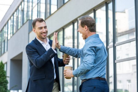 business colleagues with coffee to go giving high five near office building