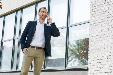 smiling businessman in formal wear talking on smartphone near office building
