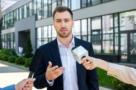 journalists interviewing serious businessman with microphones