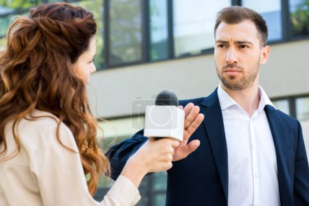 anchorwoman holding microphone while serious businessman refusing interview