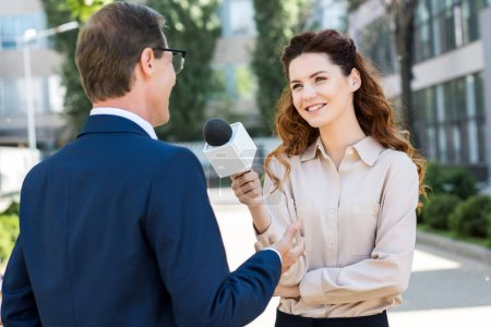 smiling female journalist taking interview with businessman