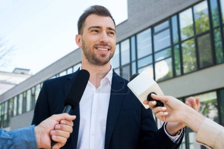 two journalists interviewing successful businessman with microphones