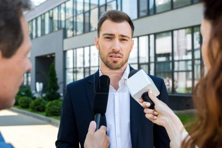 two professional journalists interviewing businessman with microphones