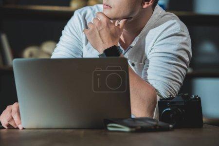 Photo pour Coup de feu recadré de jeune homme perdu dans la pensée pendant le travail sur ordinateur portable - image libre de droit