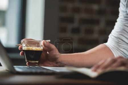 Photo for Cropped shot of  human hand holding glass of beverage while working on laptop - Royalty Free Image