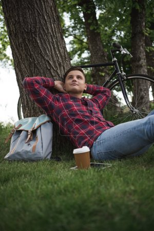 Photo for Young man enjoying summer day with coffee cup, digital tablet and bicycle behind of tree - Royalty Free Image