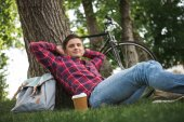 Man relaxing with coffee cup at park