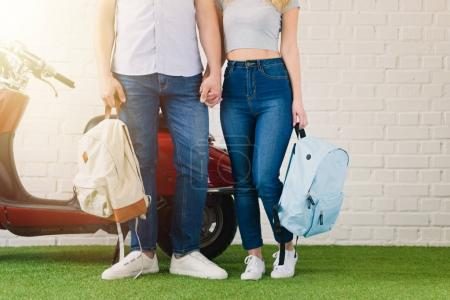 cropped shot of couple with backpacks holding hands in front of vintage scooter