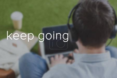 close-up shot of man in headphones using laptop, keep going inscription