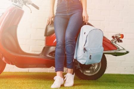 Photo pour Recadrée tir de femme avec sac à dos, se penchant sur les scooter vintage - image libre de droit