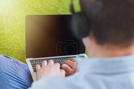 close-up shot of man in headphones using laptop