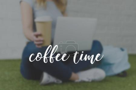 cropped shot of young woman sitting on grass with cup of coffee to go and working with laptop, coffee time inscription
