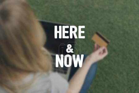high angle view of woman making e-shopping with laptop while sitting on grass, here and now inscription