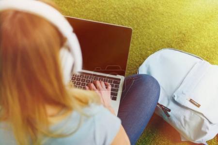 vue d'angle élevé de jeune femme assise sur l'herbe avec un casque sur la tête et travailler avec ordinateur portable
