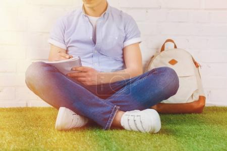 Photo pour Recadrée tir du jeune homme écrire dans cahier tout en étant assis sur l'herbe avec sac à dos - image libre de droit