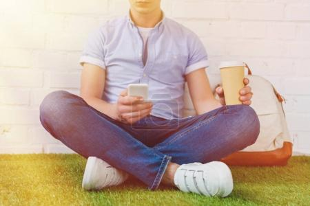 cropped shot of young man sitting on grass with smartphone and coffee to go
