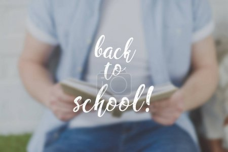 cropped shot of man reading book, back to school inscription