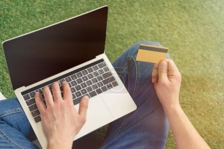 cropped shot of young man making e-shopping with notebook while sitting on grass
