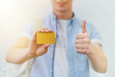 cropped shot of young man holding golden card and showing thumb up