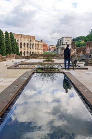 ROME, ITALY - APRIL 10, 2020: back view of man and woman standing near ancient colosseum and historical buildings