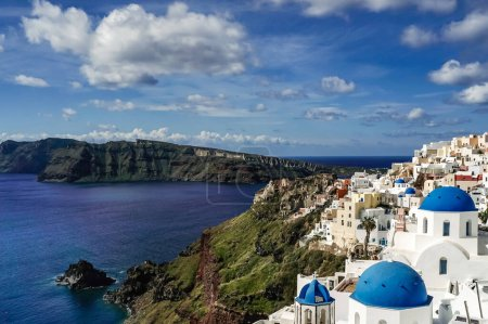 Photo for Blue-domed churches near white houses and tranquil sea in santorini - Royalty Free Image