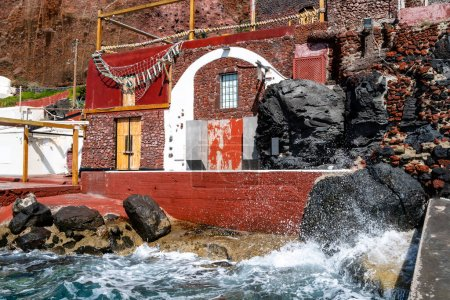 Photo pour Splash of water from aegean sea near red building on greek island - image libre de droit