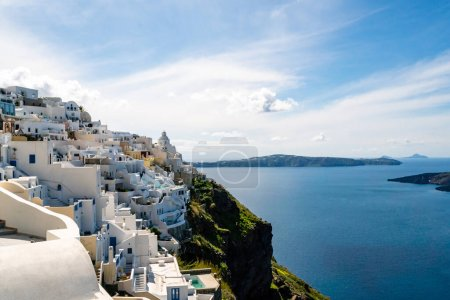 Photo for Sunshine on white houses near tranquil aegean sea against sky with clouds in Santorini - Royalty Free Image