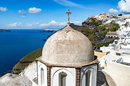 Photo for Sunlight on church near white houses and tranquil aegean sea in Santorini island - Royalty Free Image