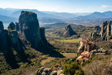 orthodox monastery on rock formations near mountains in meteora