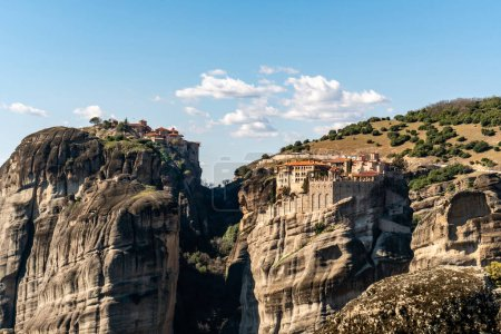 orthodox monasteries on rock formations near mountains in meteora