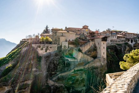 sunshine on ancient monastery on rock formations in meteora