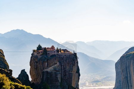 rock formations with orthodox monastery near mountains in meteora