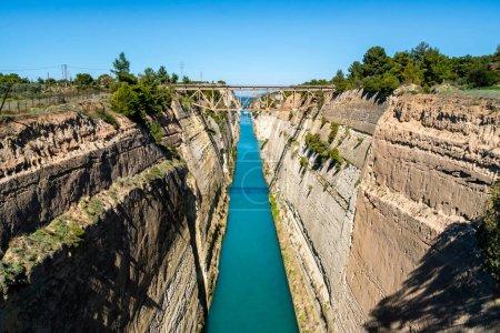 Photo pour Eau bleue coulant près des collines rocheuses avec pont - image libre de droit