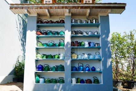 Photo pour Lumière du soleil sur les théières rétro et colorées sur les étagères près des plantes - image libre de droit