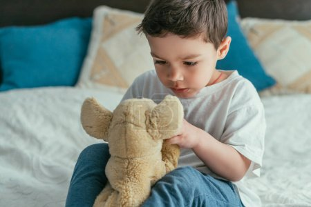 Photo for Cute toddler kid looking at soft toy in bedroom - Royalty Free Image