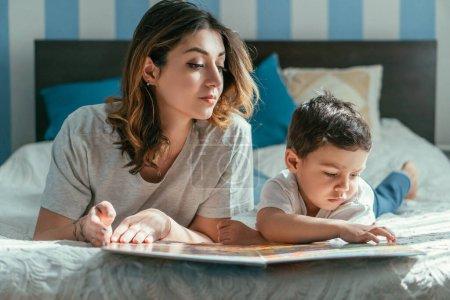 Photo pour Mignon tout-petit garçon regardant livre près de mère attrayante - image libre de droit