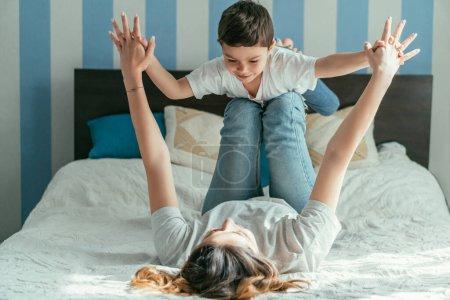 Photo pour Foyer sélectif de la mère couchée sur le lit et tenant la main avec enfant en bas âge gai fils tout en jouant dans la chambre - image libre de droit