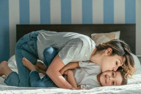 Photo for Mother kissing cheek of cute toddler son on bed - Royalty Free Image