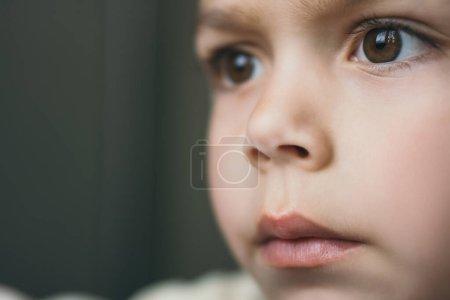 Photo pour Portrait en gros plan d'un adorable garçon aux yeux bruns regardant ailleurs - image libre de droit