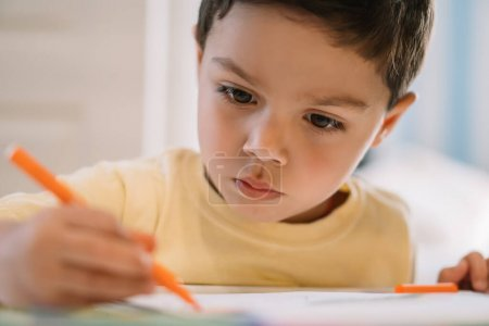 Photo for Selective focus of adorable, concentrated boy drawing with felt pen - Royalty Free Image