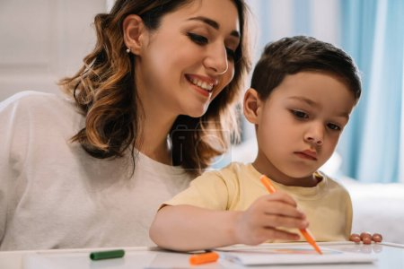 Photo for Cheerful mother looking at adorable son drawing with felt-tip pen - Royalty Free Image