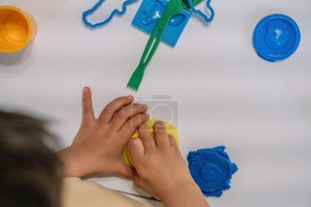 Photo pour Vue de dessus des figures de plasticine de garçon sculptant près du bâton et des moules sur la table - image libre de droit