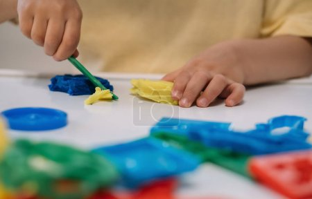 cropped view of little boy cutting colorful plasticine with spatula