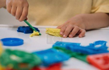 Photo pour Vue recadrée du petit garçon coupant la plasticine colorée avec la spatule - image libre de droit