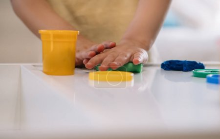 Photo for Cropped view of little boy sculpting with colorful plasticine - Royalty Free Image