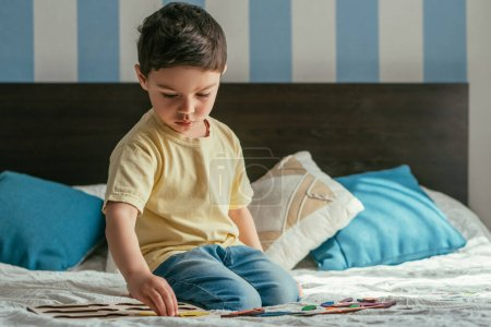 Photo for Cute, attentve kid playing board game while sitting on bed - Royalty Free Image