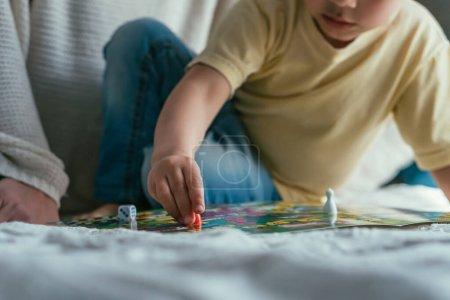 Photo pour Vue recadrée du petit garçon jouant au jeu de société sur le lit, mise au point sélective - image libre de droit