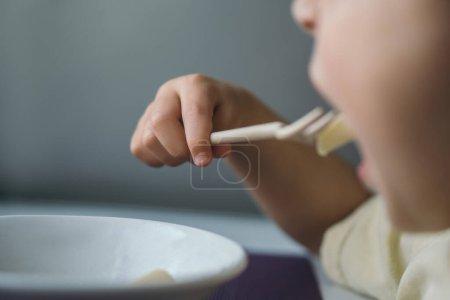 Photo pour Vue recadrée du petit garçon qui dîne en mangeant des pâtes à la fourchette - image libre de droit