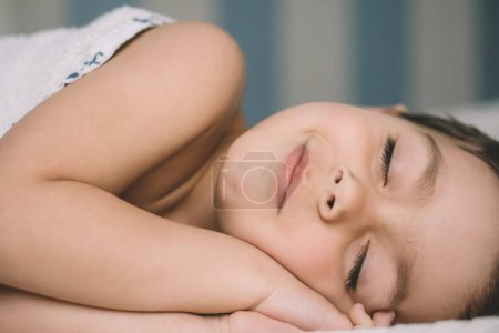 Photo for Adorable boy smiling while slipping in bed - Royalty Free Image