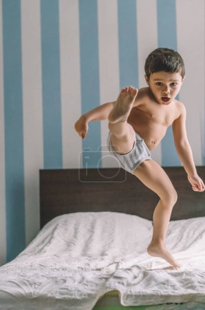 Photo for Cute boy having fun while jumping and kicking with leg on bed - Royalty Free Image